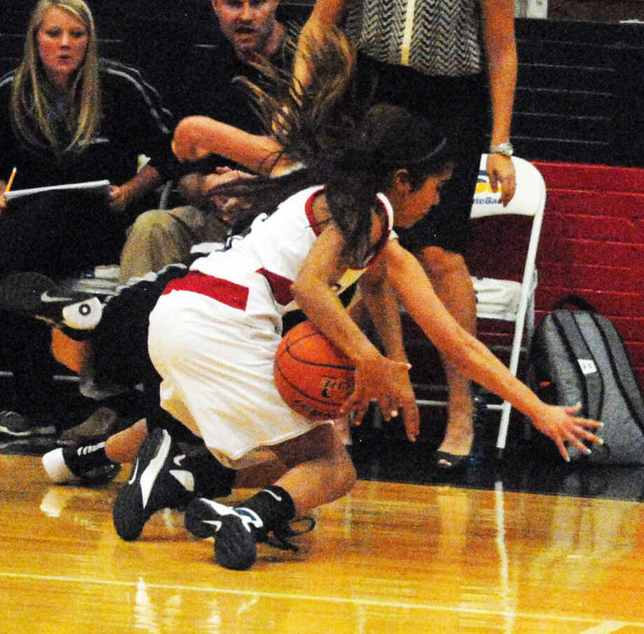 A Lady Bulldog basketball player secures the ball away from a Randall player as both fall to the floor in front of the Randall bench during the opening game of the season Tuesday night. Photo: Skip Leon/Plainview Heral