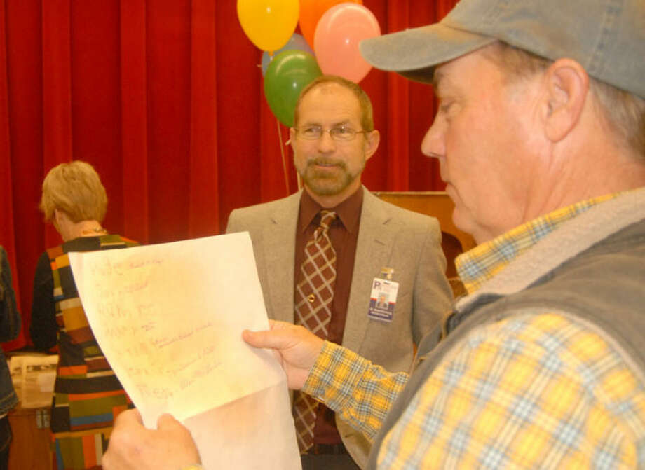 Brent Wells, who was a first grader at Edgemere Elementary when it opened in 1963, looks over a class roll bearing his printed signature during a 50th anniversary open house at the school Tuesday. Signed rosters from each classroom during the school's first year were some of the treasures tucked inside a time capsule that had spent the past half-century hidden in plain sight behind a stone plaque in the school's entrance way. Its contents were publicly revealed Tuesday. (See related story and photos on Page 1B.) Photo: Doug McDonough/Plainview Herald