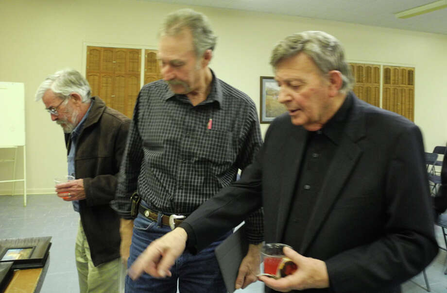 Artist Kenneth Wyatt discusses his paintings with local artist Ronny D. Green. Lockney artist Joe Garnett is at left. Photo: Gail M. Williams | Plainview Herald