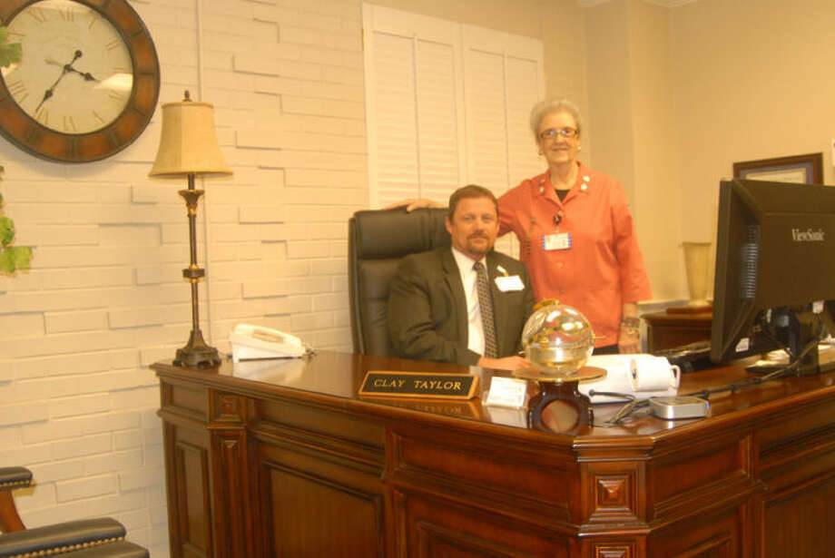 Covenant Hospital Plainview CEO Clay Taylor and Auxiliary Secretary Rose Ann Bailey pose behind the desk in Taylor's office suite which was recently refurnished through the held of the auxiliary.