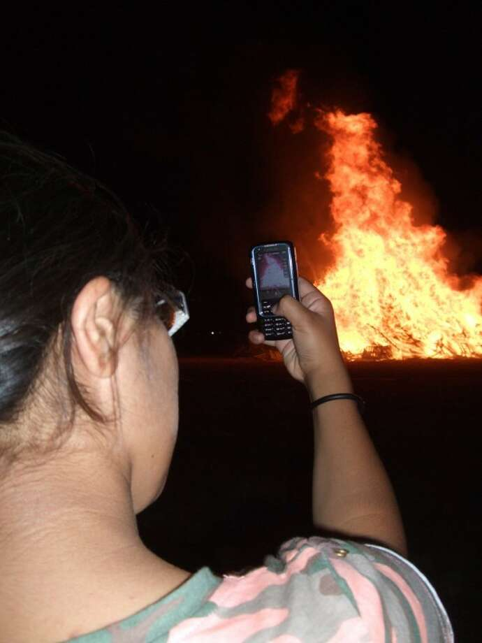 A person takes a photo of the traditional bonfire that Plainview has burned as part of its annual homecoming celebration. Because of the ongoing burn ban, this year's bonfire will be replaced with a laser show.