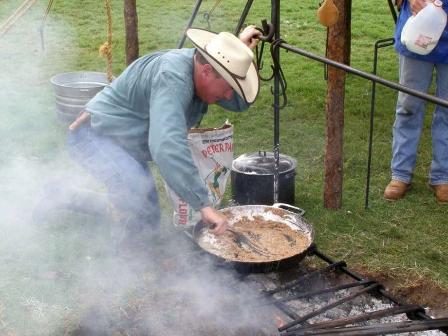 Courtesy Photos/National Cowboy Symposium & CelebrationRandy Whipple of Amarillo (above), owner of the C4B, bends over to stir a pan of beans at his C4B chuck wagon during the National Cowboy Symposium & Celebration in Lubbock. Twenty-two chuck wagons will be at this year's event.