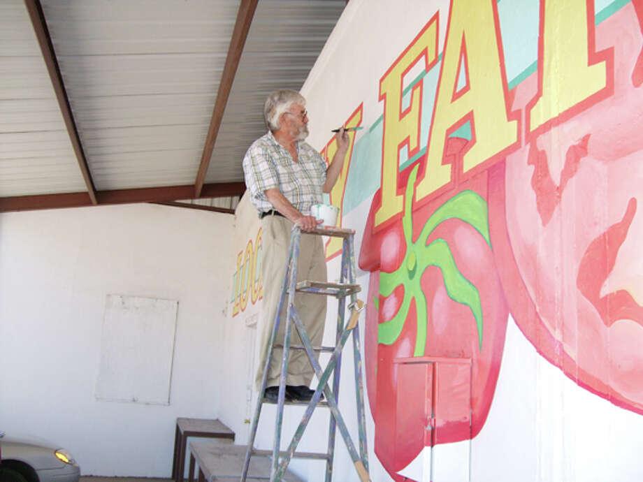 Commercial artist Joseph Garnett adds fine detail to the Farmers Market mural in Lockney.