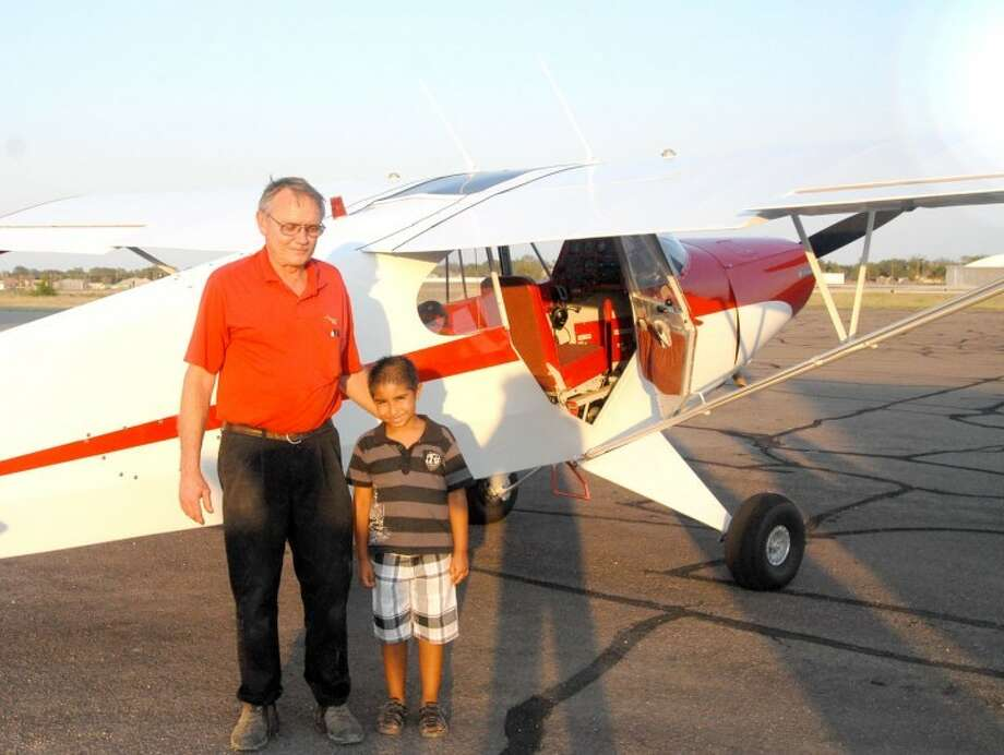 Pilot Ronnie Robbins and 7-year-old Albert Samarripa are all smiles after the pilot took the boy on his first plane ride over Hale County. Samarripa is fascinated with airplanes and it was his dream to ride on an airplane this summer. Robbins decided to give the boy a ride after reading in the Herald about his interest in becoming a pilot in the U.S. Navy. Photo: Shanna Sissom | The Herald