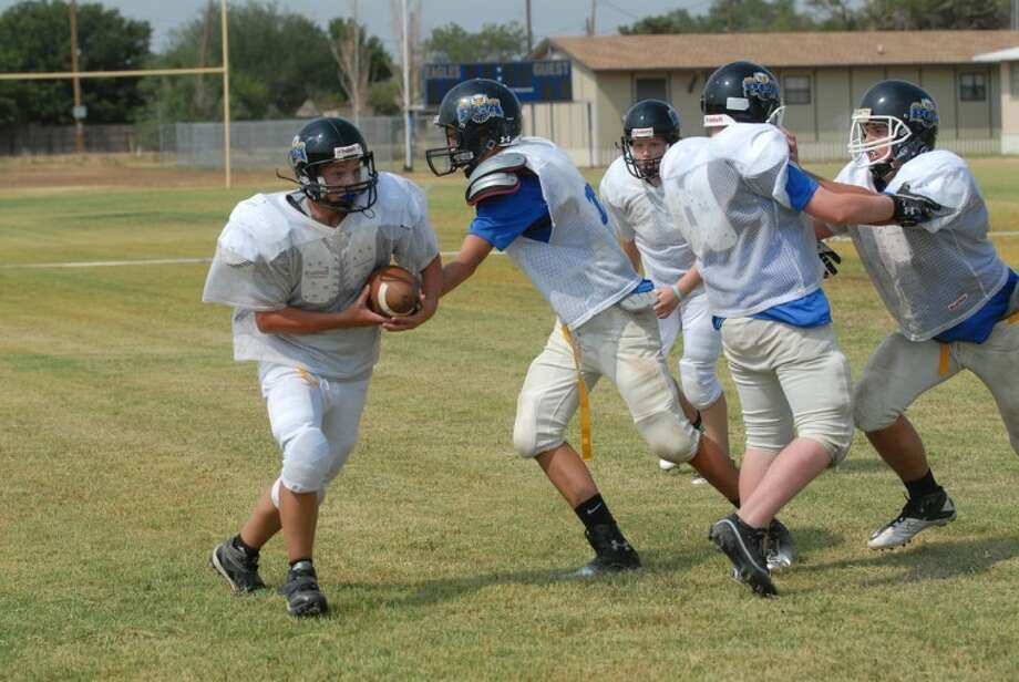 On left Bulldog defensive lineman Alvino Flores targets a running back trying to make a break. On right, Eagle Conner Smith grabs a handoff at practice Thursday . Photo: Homer Marquez/Plainview Herald