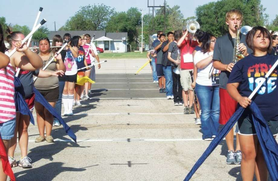 PHS band members stand at attention waiting for the next command during practice last week. The band, which held its annual march-a-thon Saturday, has been working to perfect their contest show since the beginning of August.
