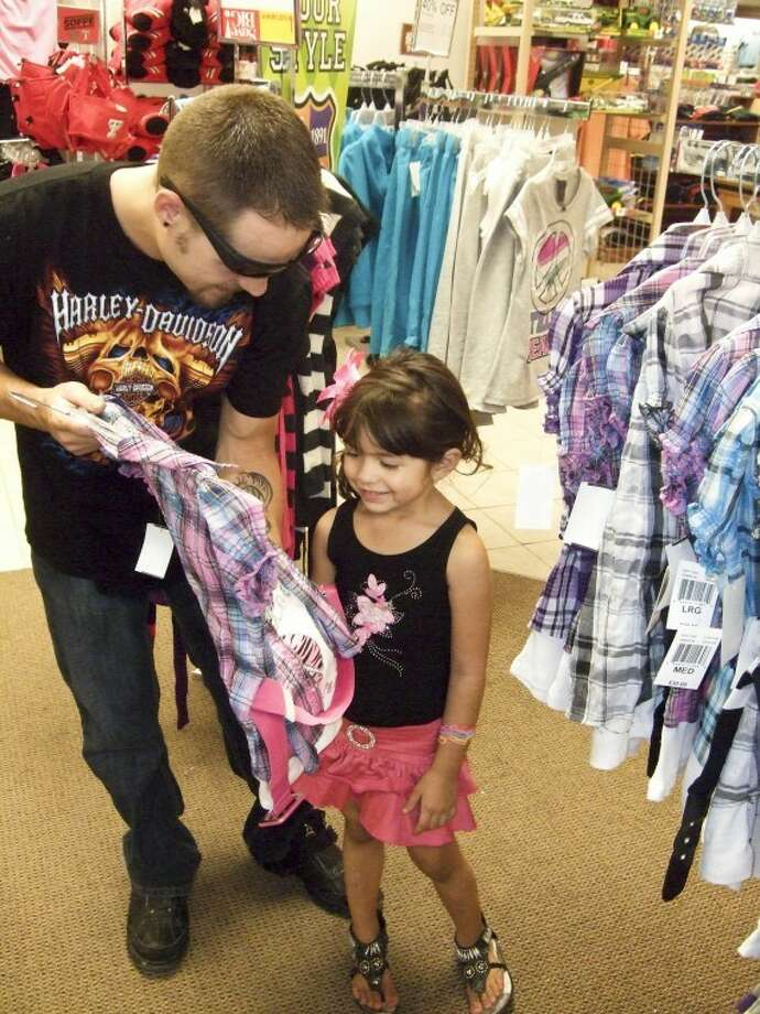 "Emily Gonzales, 5, looks over new school clothes with her dad, Matt, on Saturday evening at Beall's. Today is the last day shoppers can take advantage of the state's annual tax-free weekend. Shoppers pay no state or local sales tax on many school supplies, school backpacks and most children's and adults' clothing and shoes priced at less than $100. It's projected shoppers will save $62.1 million in state and local sales taxes during the sales tax holiday. Many stores were packed with shoppers this weekend, including Beall's where assistant store manager Selma Martinez said they were ""very, very busy."" Students return to class at most public schools on Monday, including Emily, who will be attending Edgemere Elementary."
