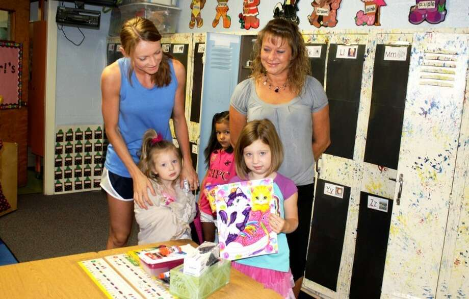 Eager to begin her first day of kindergarten this morning, Zoey Berry (front right) unpacks her new school supplies while her mom Kim Berry (left), younger sister Maya, and teacher Angie Perry watch. Zoey attends College Hill Elementary. Photo: Jan Seago Plainview ISD