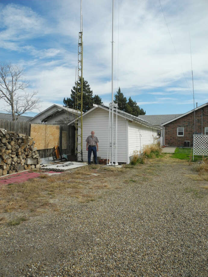 """""""Your antenna is half your radio station,"""" Ted Stone said. Here he stands between two different antennas in back of his house, a vertical and a wire antenna. Photo: Gail M. Williams 