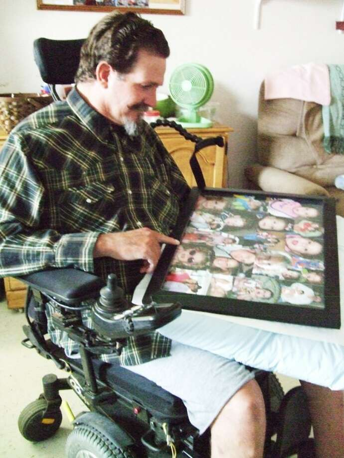 Disabled rancher Kent Winders looks at a photo montage he's hold in his lap featuring his nine grandchildren. His goal is to eventually hold those children, something he's never been able to do because of multiple sclerosis. Photo: Shanna Sissom/Plainview Herald