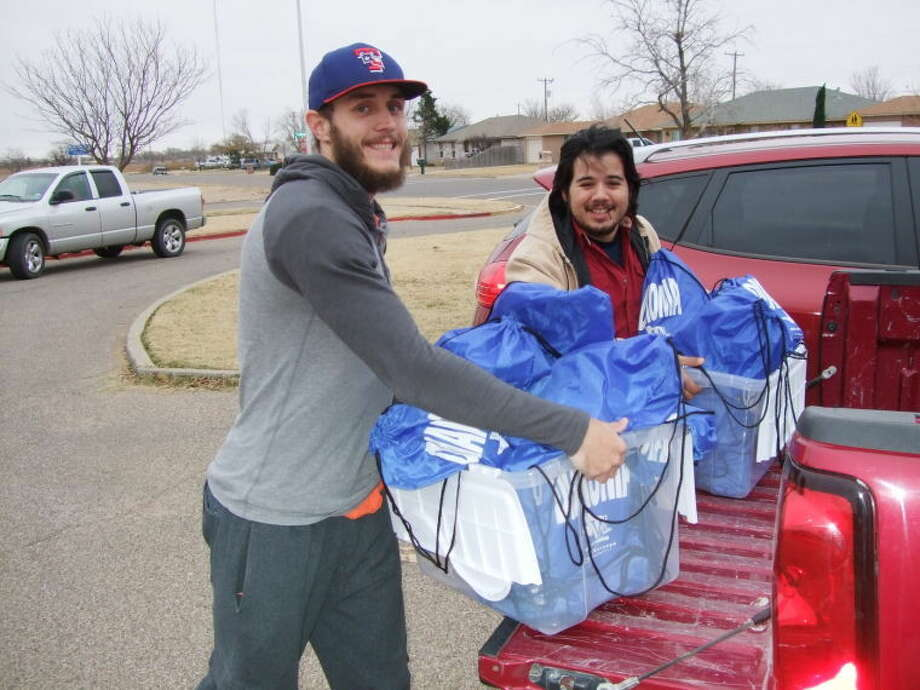 Wayland Mission Center volunteers Bryce Hollingsworth (left) and Tigo Cruz deliver weekend snack sacks for local students Friday afternoon. Photo: Homer Marquez/Plainview Herald