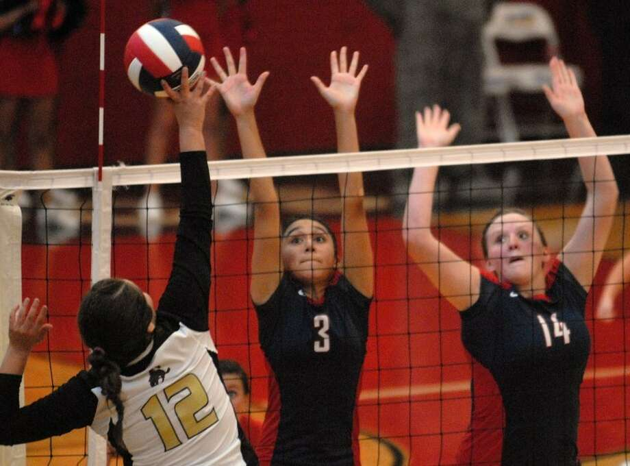 Plainview Lady Bulldogs Lupita Quintanilla (3) and Bailey Davis (14) try to block a kill attempt by Lubbock High Lady Westerner Catherine Wiechmann during a match Tuesday in the DogHouse. Lubbock High won in three games.  Photo: Richard Porter/Plainview Herald