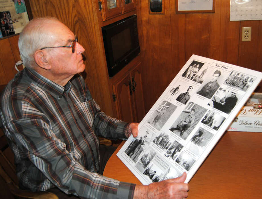 John McDonough looks over a montage of photos from his days as a member of the 554th Anti-Aircraft Battalion during World War II. The retired local building contractor was a corporal who served in headquarters battery as the unit's mail clerk. Photo: Doug McDonough/Plainview Herald