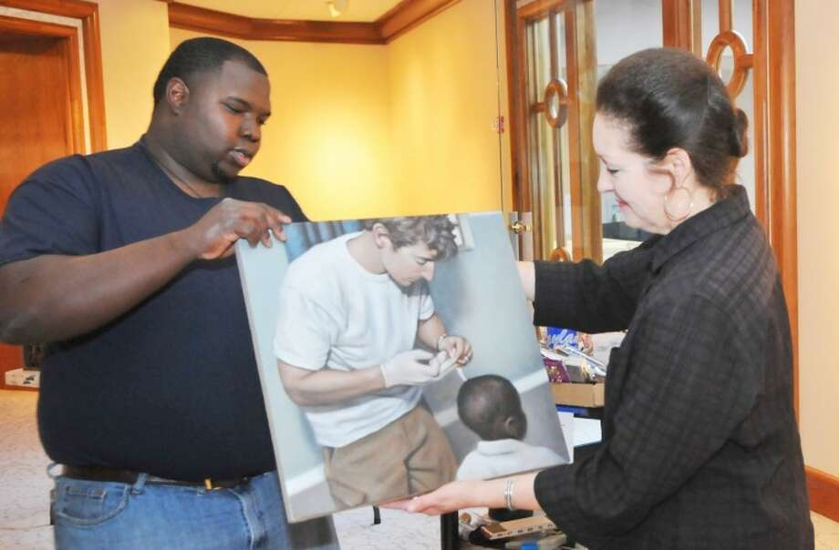 """Abraham Art Gallery assistant Jay Coleman helps Dr. Candace Keller, professor and curator of art, hang one of the pieces for the """"Work: Curse or Calling?"""" show which will be on display in the gallery beginning Monday and running through Oct. 6. Photo: Wayland Baptist University"""