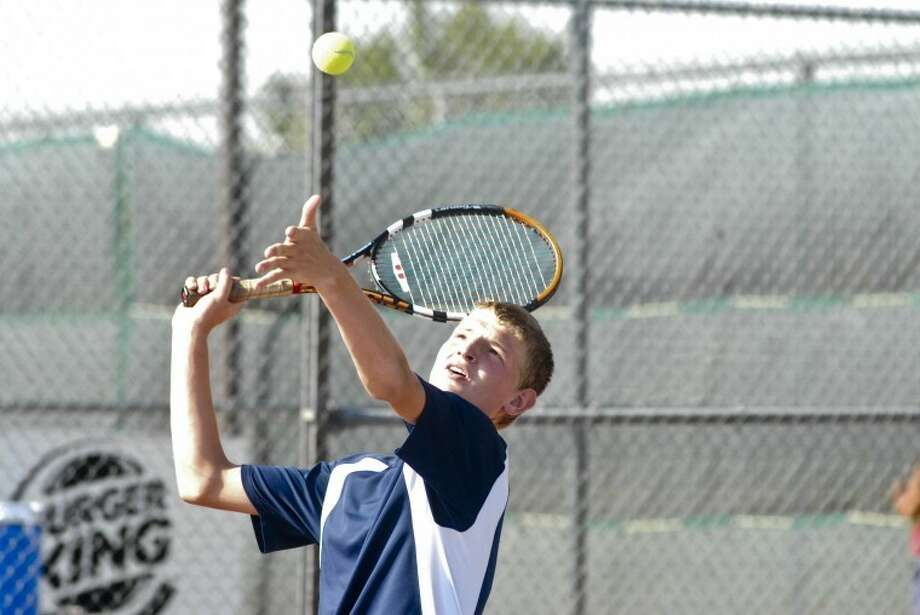 The Plainview Bulldogs' Jeremy Brush tosses the ball for his serve during a doubles match Saturday in Plainview against a team from Pampa. Photo: Ryan Thurman/Plainview Herald