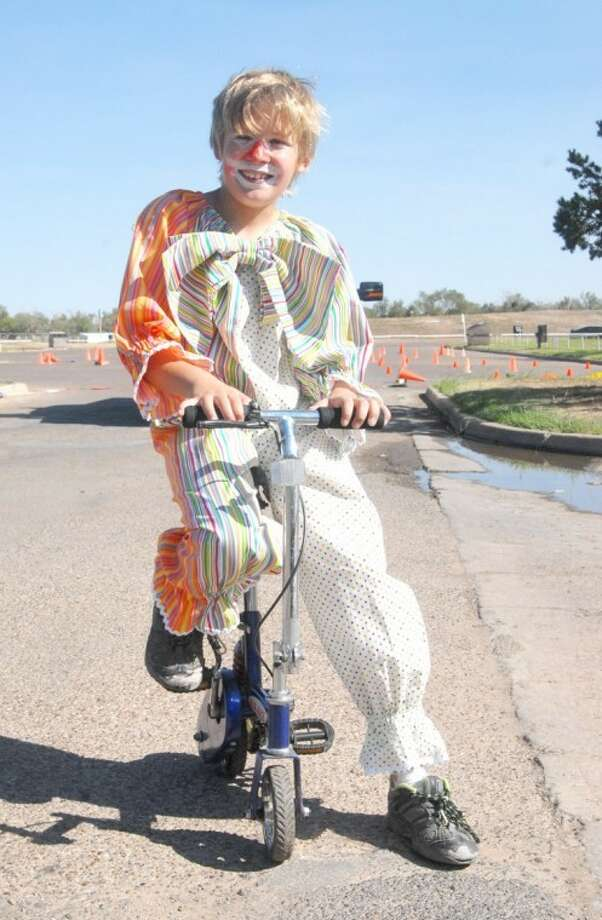 Eleven-year-old Ryan Andrae dressed in a clown costume to ride a mini-bike to the hk2020 event Tuesday. Photo: DOUG McDONOUGH