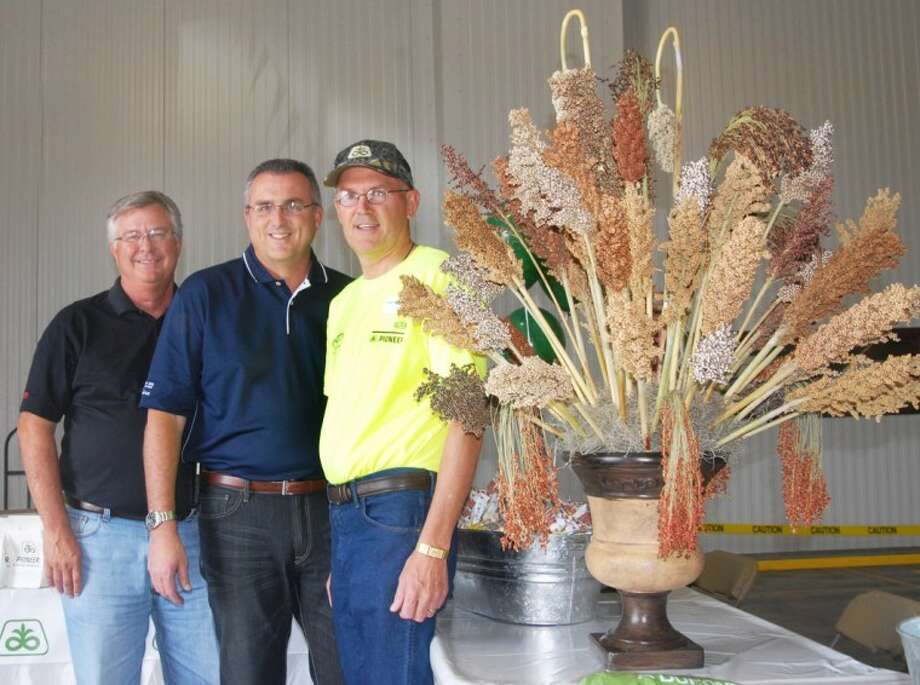 Gathering around a grain sorghum bouquet during Thursday's open house marking the 50th anniversary of DuPont Pioneer in Plainview are Mike Glenn (left) of Lubbock, area sales manager; Steve Reno of Lincoln, Neb., Western Business Unit director; and Leon Heinen, Plainview production location manager. Photo: Doug McDonough/Plainview Herald