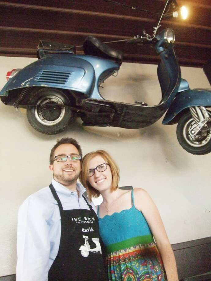 Stacey and David Splawn are seen inside their Broadway Brew next to the trademark scooter they rode together when dating.