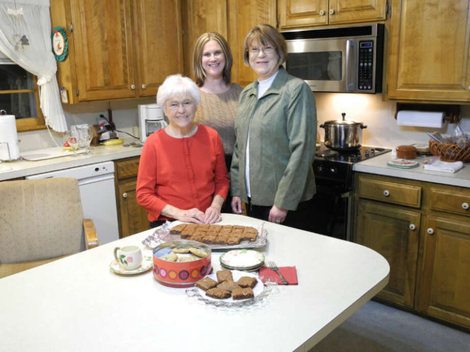 """Mildred Brown, left, her granddaughter Melinda Brown and daughter-in-law Brenda Brown were all instrumental in publishing the cookbook that pays tribute to Lillie Houchin, called """"Mama Hooch,"""" who passed her love of cooking, her methods and her recipes down through the generations. Photo: Gail M. Williams   Plainview Herald"""