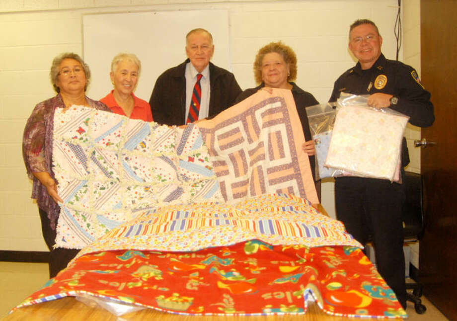 Mary Sanchez (left), Frances Sawaya, Police Chief Will Mull, Cindy Ozborn Wolfe and Police Capt. Derrick McPherson look at the first group of quilts delivered Wednesday to the department to give to young children involved in crisis situations. Photo: Doug McDonough/Plainview Herald