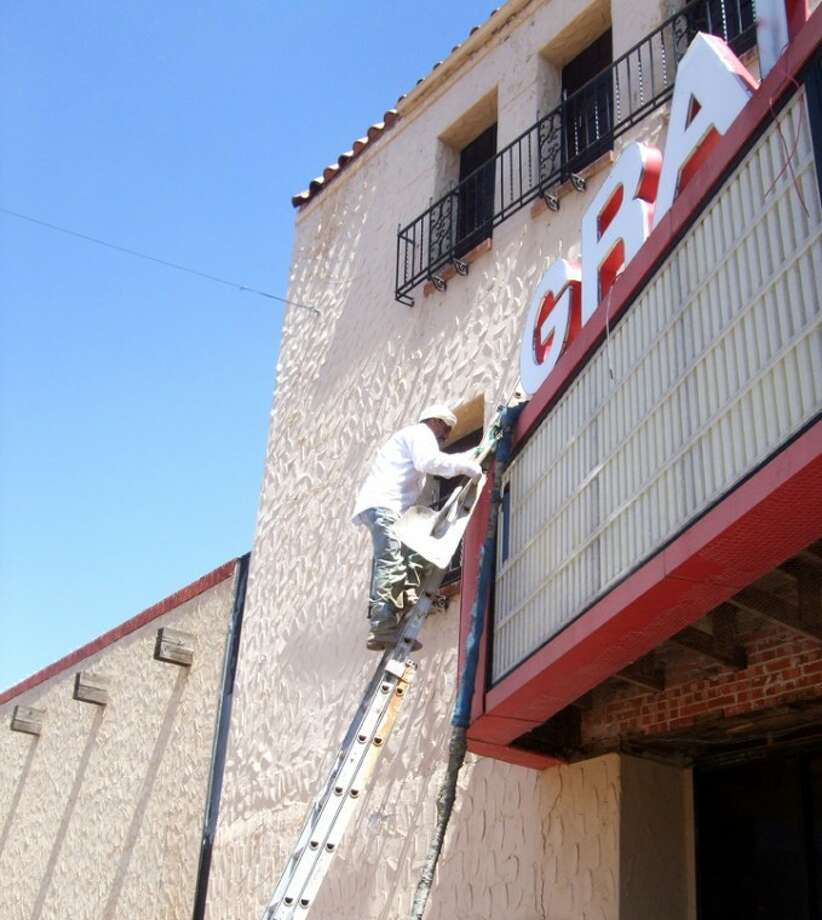 Shanna Sissom/Plainview HeraldA Dickerson Roofing company employee works from a ladder to make repairs last week to the marquee at the Granada Theater.