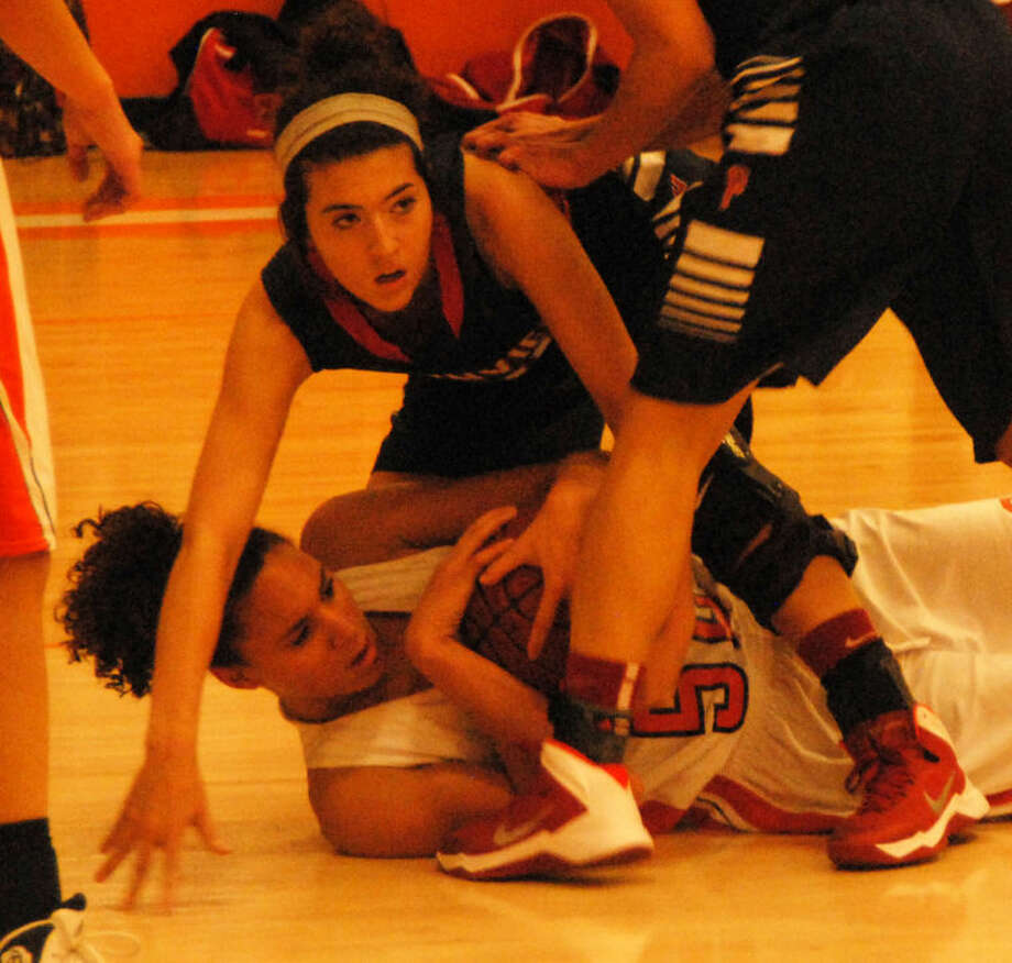 A Caprock player clutches the ball on the floor as Plainview's Shalee Bennett tries to wrestle it away from her during a girls basketball game in Amarillo Friday night. Photo: Doug McDonough/Plainview Herald