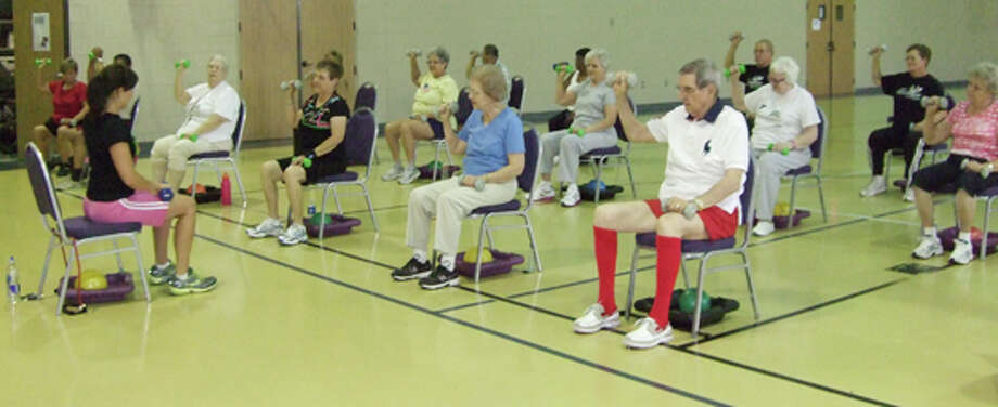 Members work out with weights to improve arm and shoulder strength. Photo: Gail M. Williams | Plainview Herald
