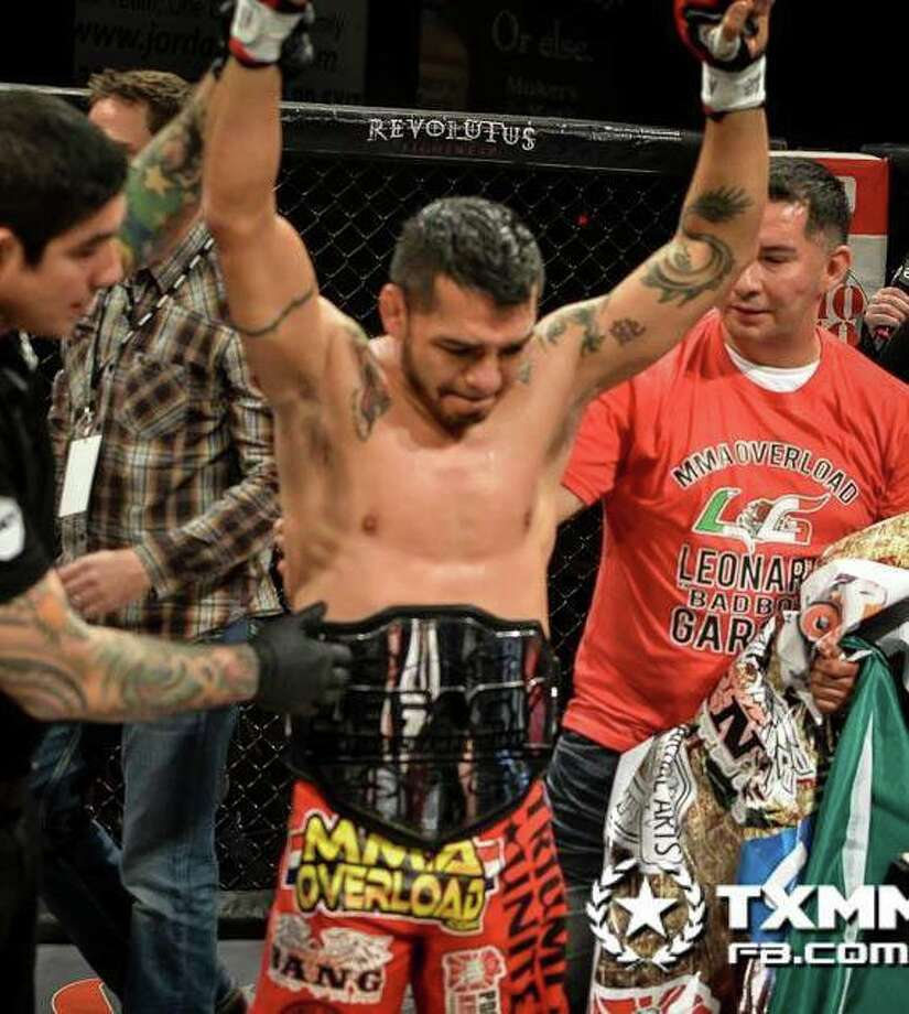Leonard Garcia raises his arms in victory after winning the Legacy Fighting Championship (LFC) featherweight championship Dec. 6. Photo: Photo Courtesy Of TXMMA.com