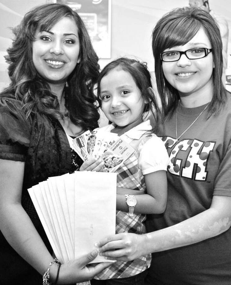 Demi Sandoval and daughter Savannah Arredondo, 5, show off a one-year supply of hamburger coupons along with Marisol Gloria of Plateau Wireless. Demi won a recent charity event to boost the area's Ronald McDonald House Charities. Burgers were donated by Rick and Ruth Robillard, owners of the Plainview McDonald's while Plateau set up registration boxes for the burger drawing and made a $10 contribution to RMHC for each new customer activation in an effort to raise $8,000 during July.