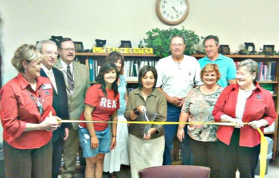 The Hale County Literacy Council last week held a ribbon-cutting ceremony at its new offices at Houston School. Shown are (front, from left) Chamber Red Coat Janis Roberson, Mayor John C. Anderson, HC-Jr. Board President Melissa Rau, HCLC Director Lydia Castillo, Houston School Principal Dana Broyles, Chamber Red Coat Janice Payne; (back) PISD Supt. Dr. Ron Miller, HCLC Board member Diane Book, Perry Gruhlkey and State Rep. Jim Landtroop. Giveaway winners were Sylvia Barrera, who won a Nook, and Letti Cheyne, who won a Kindle.