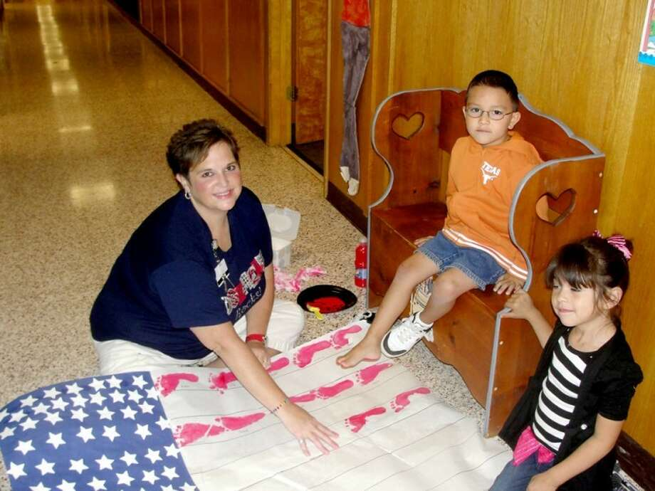 With help from Edgemere Elementary pre-kindergarten teacher Amy Kitchens, Aden Alarcon makes a footprint while Emily Gonzales waits her turn as the class constructs a U.S. flag in honor of the 10-year anniversary of the Sept. 11 terrorist attacks. Photo: Teresa Kinkaid Edgemere Elementary