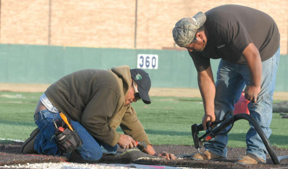 Juan Alvarado (left) and Jorge Silva install artificial turf on Wilder Field at Wayland Baptist University Wednesday afternoon. The duo is part of a six-man crew from Swank Sports in Bastrop who are putting in the turf. They began the job last Friday and expect to finish Friday or Saturday. The turf will see use Jan. 11 when Wayland Baptist holds a baseball tryout. Photo: Skip Leon/Plainview Herald