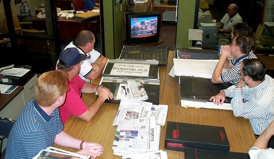 Members of the Herald staff gather around the television to watch as the terror attack unfolds on Sept. 11, 2001, while Herald Managing Editor Doug McDonough (upper right) works to update Page 1. Photo: Richard Porter Plainview Herald