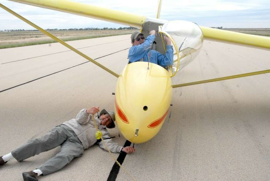 Dr. Michael Graves, a glider instructor and urologist, checks the rope fastener as Geoff Wells, a Wayland professor, prepares for another glider lesson.  Photo: Shanna Sissom/Plainview Herald