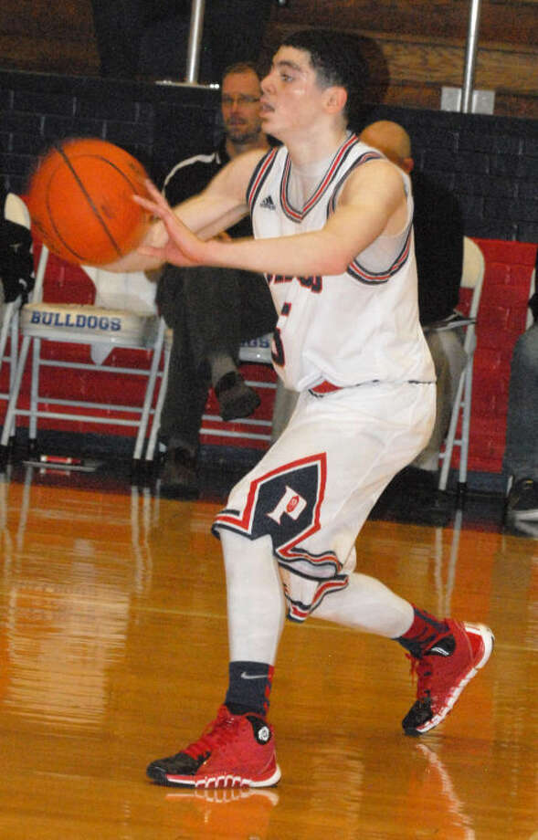 Jayton Ellis passes the ball during Plainview's victory over Randall at the Dog House Friday night. Ellis, a sophomore point guard, led the Dogs with 18 points, six assists and five rebounds. Photo: Skip Leon/Plainview Herald