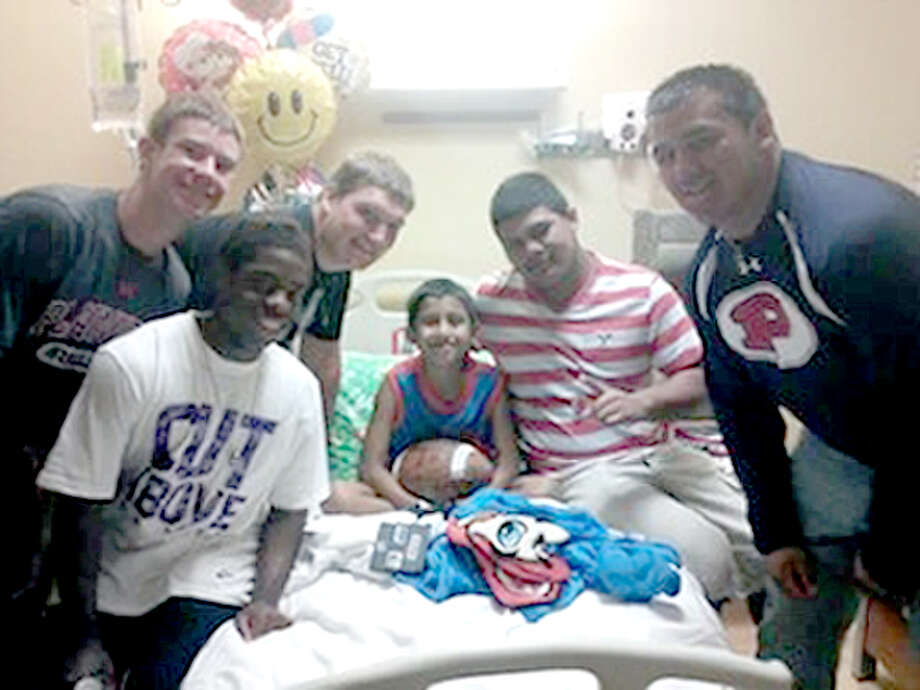 Plainview Bulldogs football players Shirmar Jennings (left), Wes McCutcheon, Jacob King, Christian Galvan and Coleman Townsend visit 9-year-old Josiah Champion at a Lubbock hospital. The players delivered a football signed by the team to the Highland Elementary fourth-grader, who is undergoing chemotherapy treatments while battling lymphoma.