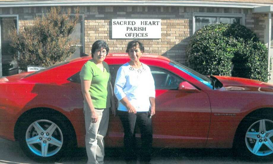 Raquel Hernandez (right) poses with the 2011 Chevy Camaro she won last weekend in a raffle at Sacred Heart Catholic Church. Also pictured is Rosie Rodriguez, who sold Hernandez the winning ticket. Sacred Heart members appreciate everyone who bought a ticket to support the church.