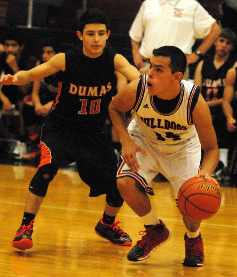 Desmond Vera (right) dribbles against a Dumas player in a game earlier this season. Vera leads the Bulldogs in rebounding and is shooting 62 percent from the field. Photo: Skip Leon/Plainview Herald