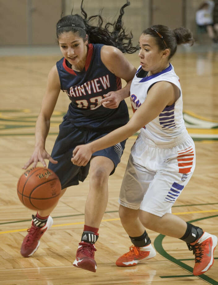 Plainview's Karli Wheeler drives around Eastlake's Caitie Aguirre Saturday in the girls championship game of the Bryon Johnston Holiday Classic in Midland. Wheeler scored 13 points in the championship game and was named the tournament's Most Valuable Player in leading the Lady Bulldogs to their 11th tourney championship. Photo: Tim Fischer/Midland Reporter-Telegram