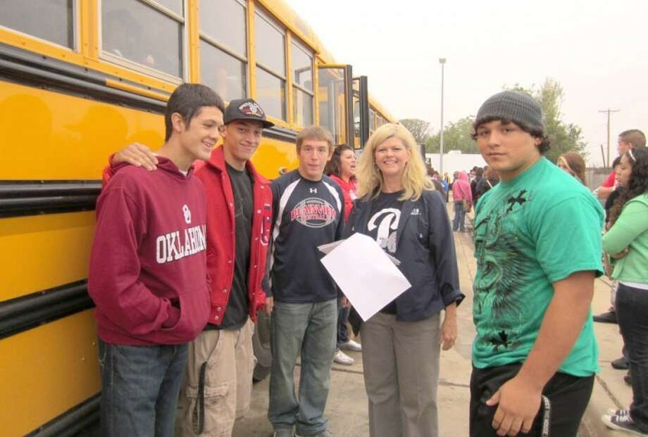 PHS seniors Stratton Mowry (left), Jordan Masters, Kory Mansell and Greg Marroquin check their bus assignments with Lisa Kersh, director of curriculum, before boarding buses to South Plains College on Friday. More than 250 members of the senior class and 10 sponsors made the trip to Levelland. Students spent the day touring the campus, visiting technical programs and getting acquainted with life on a college campus. South Plains Bank in Levelland provided lunch for the students and sponsors.
