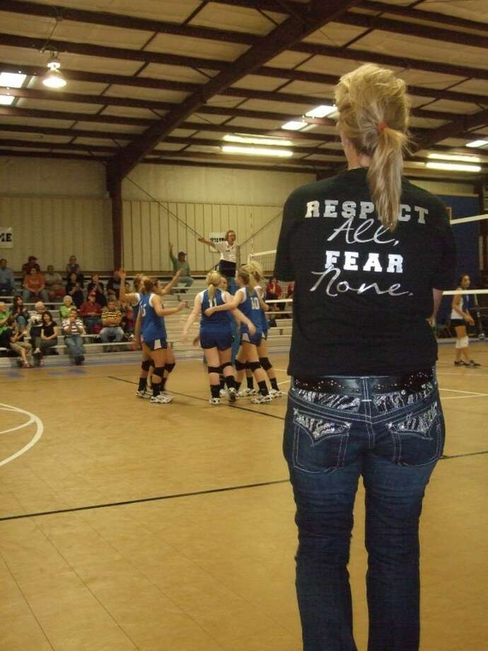 """Plainview Christian Lady Eagles' coach Bernadette Mulliken looks on as the Lady Eagles celebrate a point during a match against Amarillo Ascension in the Eagles' Nest on Tuesday. Mulliken's shirt, which states """"Respect All, Fear None"""" is the team's motto for the season. Photo: Kevin Lewis/Plainview Herald"""