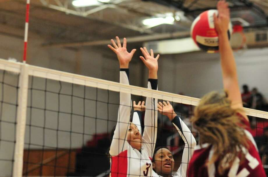 The Plainview Lady Bulldogs' Lupita Quintanilla (left) and Tai via Hearn (center) try to block Hereford's Audrey Forester during a District 3-4A match on Tuesday in the DogHouse. Photo: Ryan Thurman/Plainview Herald