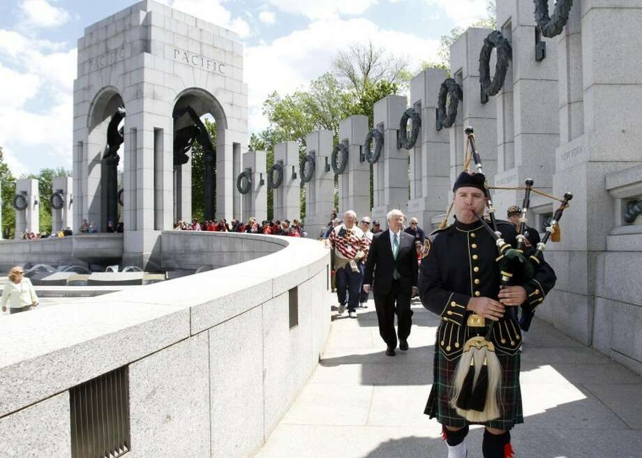 Daniel Loughnane plays the bagpipes as he leads Mississippi Gulf Coast Honor Flight veterans into the World War II Memorial April 24 in Washington, D.C. Photo: Tim Isbell/Biloxi Sun Herald/MCT