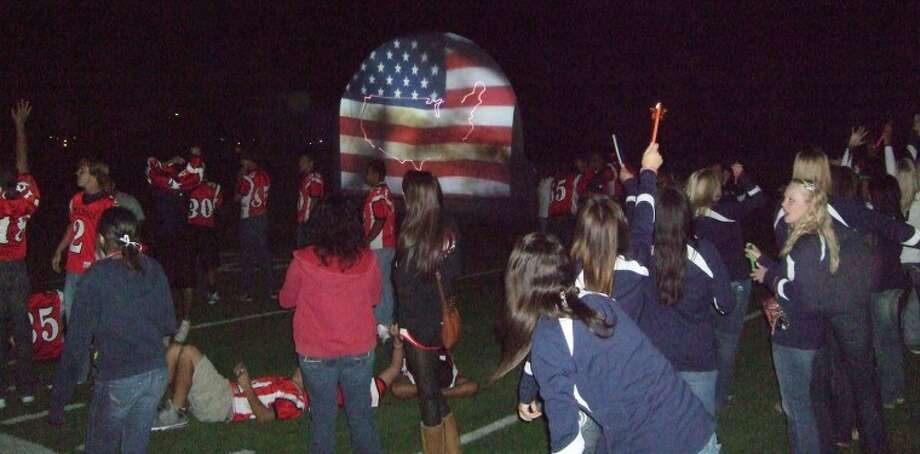 Members of the Plainview Bulldog football team and other PHS athletes gather on the field at Greg Sherwood Memorial Bulldog Stadium near the conclusion of Thursday night's patriotic-themed laser show, sponsored by the Red Rage and PHS band booster clubs. The show was in response to the county-wide burn ban that prevented a homecoming bonfire. (See related video.)