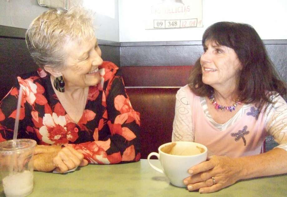 Janie Malone (left) and Karen Henderson, both breast cancer survivors and members of the American Cancer Society's Reach for Recovery, enjoy coffee recently while reflecting on their journey. The two women offer support and mentorship to women newly-diagnosed with breast cancer. Photo: Shanna Sissom/Plainview Herald