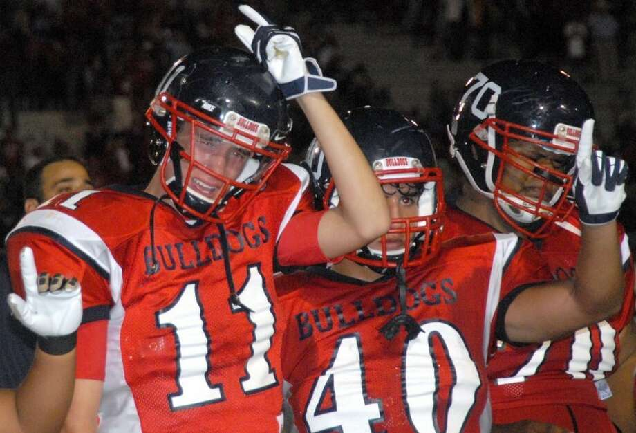 Plainview Bulldogs Brooks Cannon (11), Adrian Gonzalez (40) and Corey Williams react while listening to the school song after losing 36-35 to the Dumas Demons on a last-second Hail Mary pass Friday night at Greg Sherwood Memorial Bulldog Stadium. Photo: Richard Porter/Plainview Herald