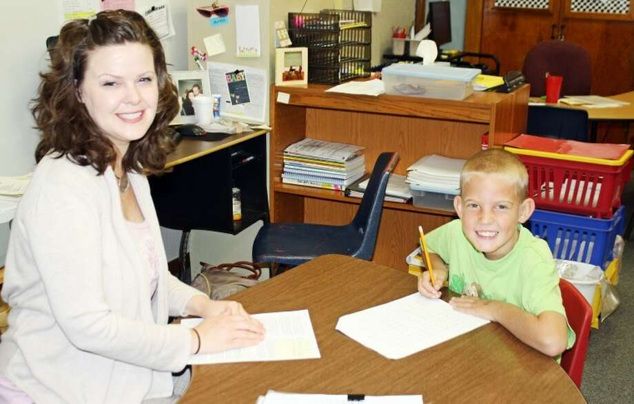 Highland Elementary assistant Holly Warren assists Bo Autry as he catches up on some work he missed during the first weeks of school. Photo: Jan Seago/Plainview ISD