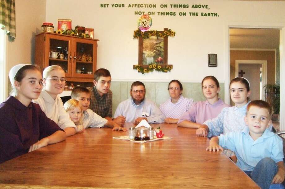 The Martin family gathers at their table in Halfway, as a neighbor child (on the left) also joins them. The Mennonite family is devoted to their Christian faith, and avoids worldly influences that would distract them from God. Photo: Shanna Sissom/Plainview Herald
