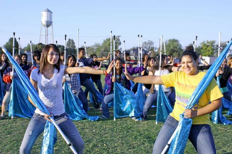 Color guard captains Brittney Ruiz (left) and Olivia Tinoco practice poses with the 30 members of the Plainview High School Powerhouse of the Plains Marching Band color guard. The team competed in the West Texas Auxiliary Championship last weekend in Lubbock where they took first place honors in the 4A classification. They also were named outstanding flag line overall for the large school category. Photo: Jan Seago/Plainview ISD