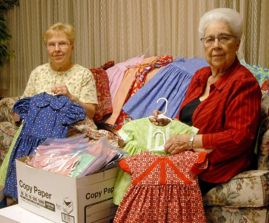 Beverly McDonald (left) helps Joanne Clevenger pack dresses Clevenger and Wanda Miller made to give to young girls in Nicaragua. The pair made 219 dresses, while Miller also made 64 boys shirts and 20 baby blankets. Photo: Richard Porter Plainview Herald